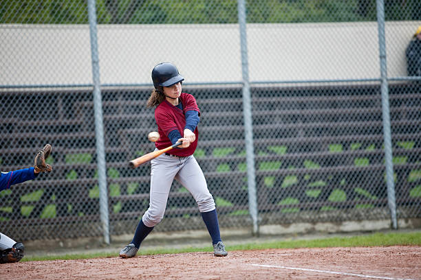 youth league batter hitting baseball - softball stock photos and pictures