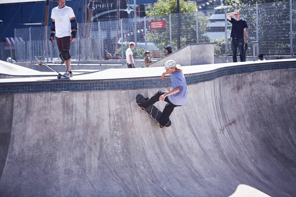 A youth performs a skateboard trick at a skatepark stock photo
