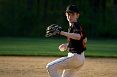 Youth pitcher winding up on the mound and about to throw