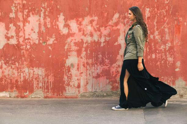 jeugd mooie vrouw op straat in de buurt van de rode muur - street style stockfoto's en -beelden