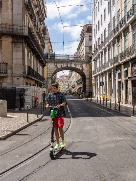 Youth riding a Lime electric scooter along Lisbon street stock photo