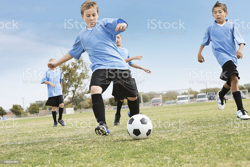Youth soccer team kicking ball during game stock photo