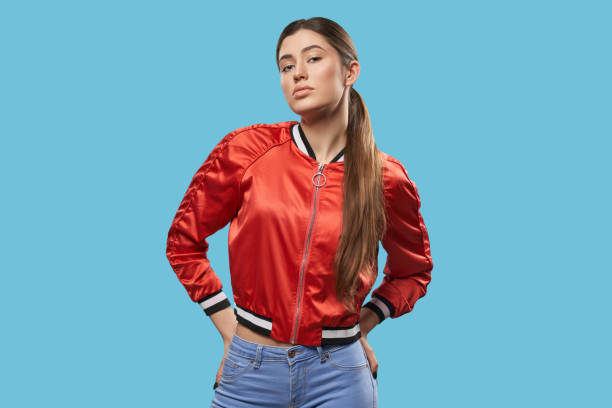 Youth style. Portrait of model in bright red bomber. Portrait of young female model on blue background. Pretty girl with beautiful make up, long hair, ponytail, wearing in bright red bomber posing and looking at camera. Youth style. bomber plane stock pictures, royalty-free photos & images