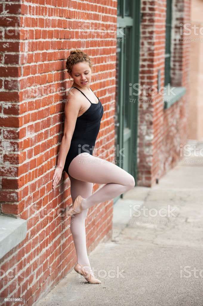 Youthful ballet girl against old building stock photo