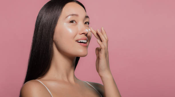 Youthful female model applying moisturizer Close up of a youthful female model applying moisturizer to her face. Young korean woman putting moisturizer cream on her pretty face against pink background. korean ethnicity stock pictures, royalty-free photos & images
