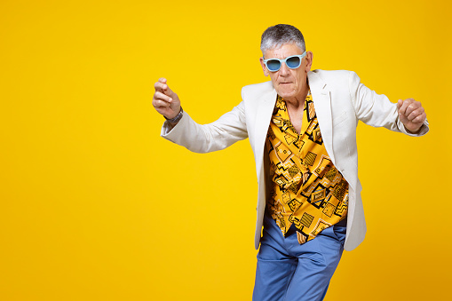 Funny and extravagant senior man dancing on coloured background