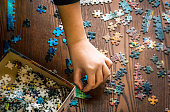 istock A youth's hand collects and assembles puzzle pieces of a jigsaw on a wooden background. background selective blur, concept 1191774717
