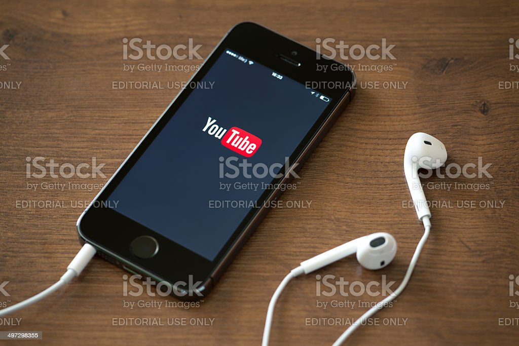 YouTube application on Apple iPhone 5S Kiev, Ukraine - June 5, 2014: Brand new Apple iPhone 5S with YouTube application service on the screen lying on a desk with headphones. YouTube is the world's most popular online video-sharing website that founded in February 14, 2005 YouTube Stock Photo