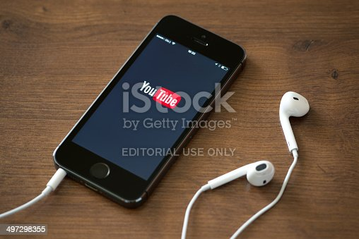 Kiev, Ukraine - June 5, 2014: Brand new Apple iPhone 5S with YouTube application service on the screen lying on a desk with headphones. YouTube is the world's most popular online video-sharing website that founded in February 14, 2005