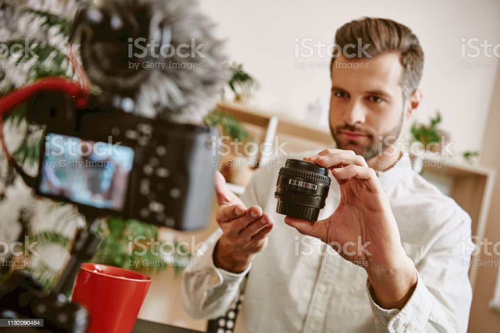 Youtube channel. Young bearded blogger showing camera lens to camera and speaking about its advantages and disadvantages stock photo