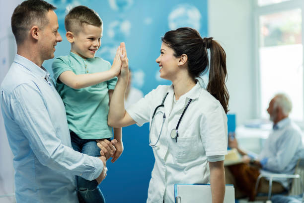 You've been really brave today! Happy female doctor giving high fie to a little boy who came with father at hospital. medical clinic stock pictures, royalty-free photos & images