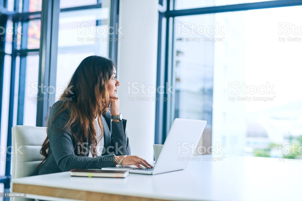 You've come far, now go further Shot of a young businesswoman using a laptop and looking thoughtful in a modern office 20-29 Years Stock Photo