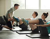 Shot of a young male trainer taking his clients through a fitness routine in the gym
