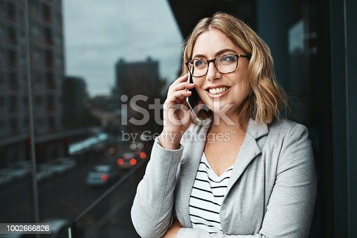Shot of a young businesswoman talking on a cellphone on the office balcony