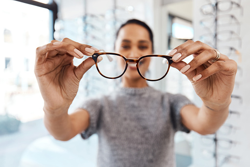 Shot of a young woman buying a new pair of glasses at an optometrist store