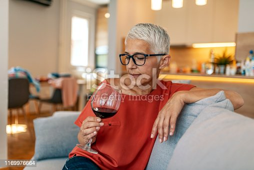 Photo of mature sad woman sitting on sofa with one glass of red wine waiting for somebody (man) - loneliness, quarrel, celebration Valentine Day alone concept. Lonely mature woman holding glass of alcoholic drink while sitting on sofa at home during the day.