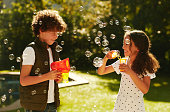 Shot of an adorable brother and sister blowing bubbles together outdoors