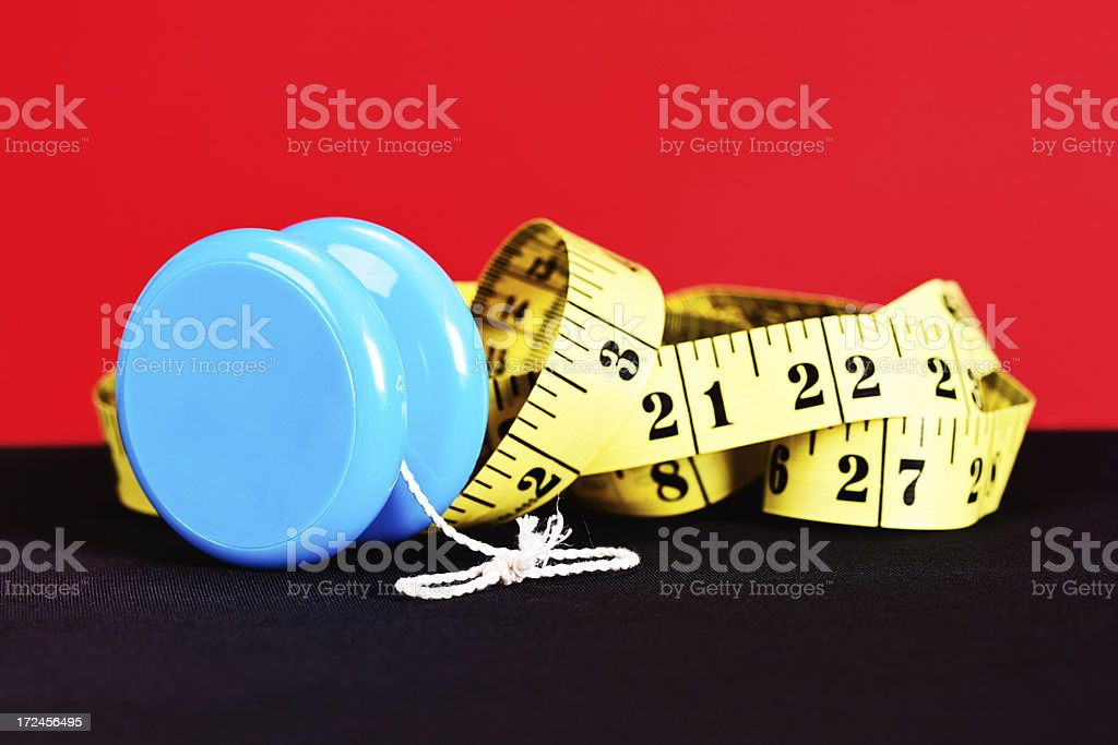 Yo-yo and tape measure demonstrate on-off dieting does not work! royalty-free stock photo