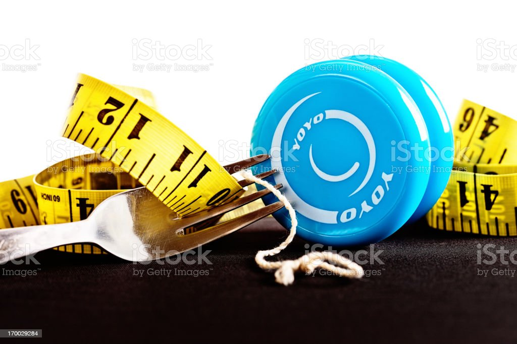 Yo-yo dieting with tape measure and fork stock photo