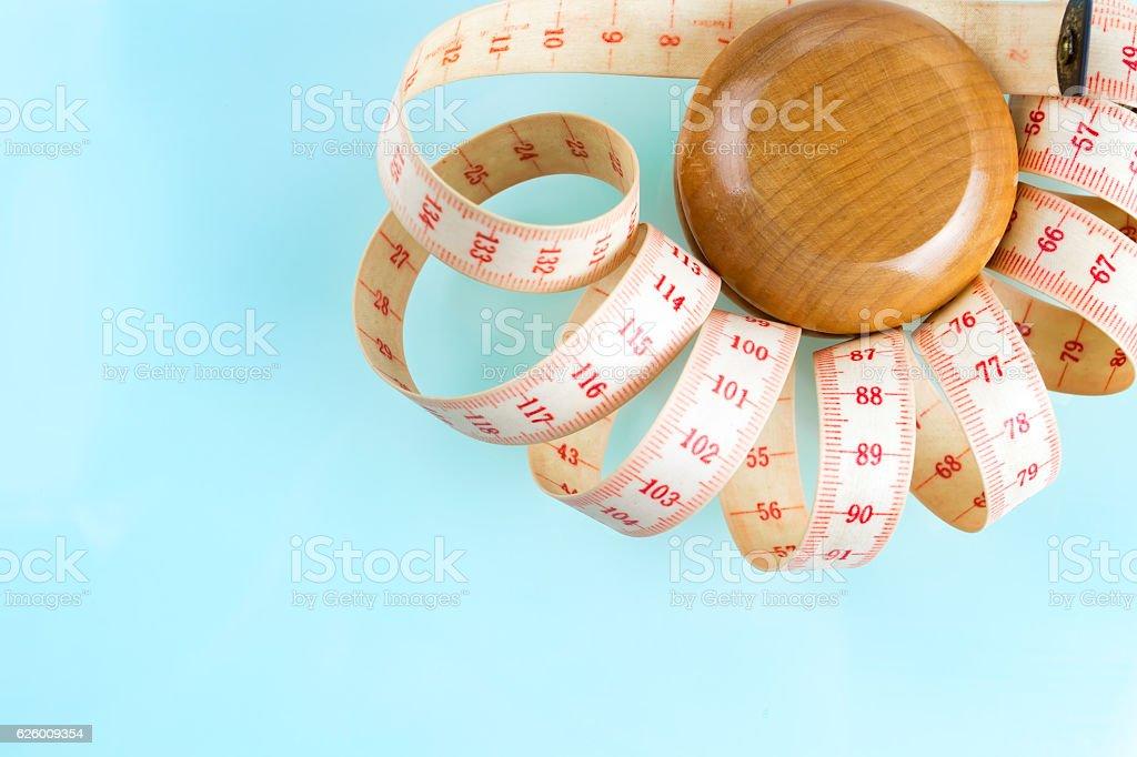 Yo-yo effect concept. Wooden yoyo with centimeter measure. stock photo