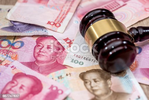 1024130248istockphoto yuan on wooden hammer . close up. 667747832