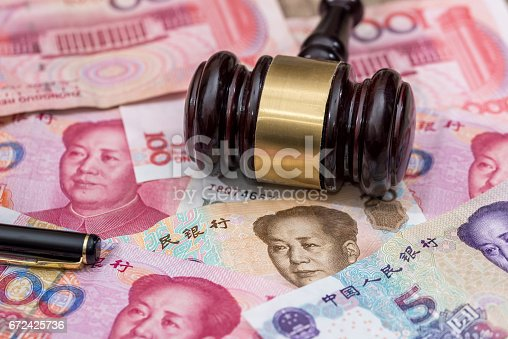 1024130248istockphoto yuan on wooden hammer . close up. 672425736