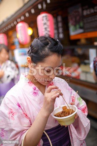 Yukata woman tasting simmered pork innards on street at festival