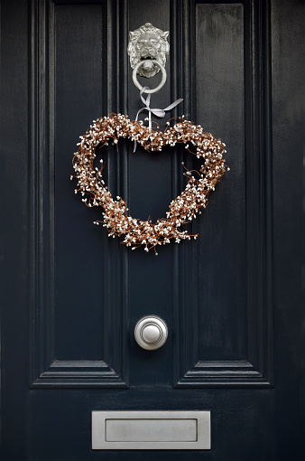 Traditional Decorative Yule Christmas wreath in a heart shape on a Victorian Front with period (19th century) knocker and letter box door in London, UK