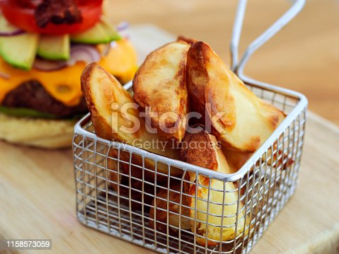 Closeup shot of fried potato wedges in a chip basket on a cutting board in the kitchen during the day