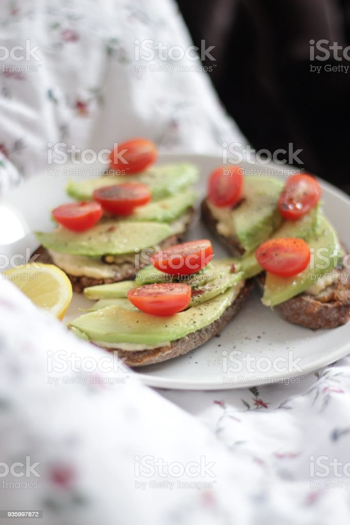 Photo of three well done toasts with hummus, avocado, pepper, salt,...