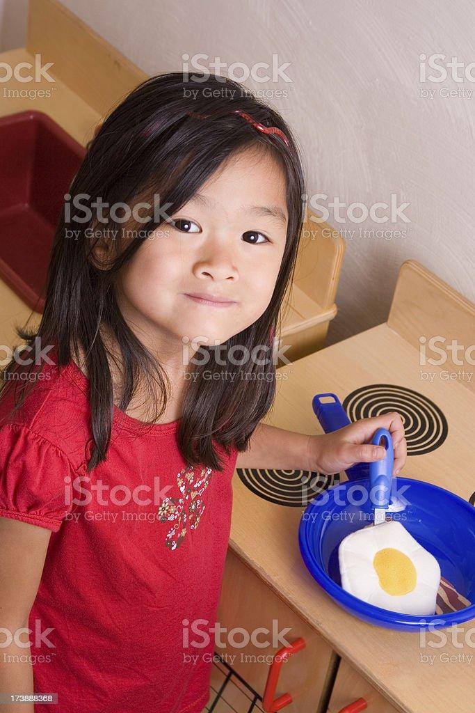 Yummy Breakfast Chinese little girl cooking pretend breakfast 6-7 Years Stock Photo