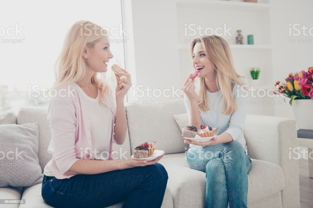 Yummy! Cheerful laughing mother and daughter eating nutrition food delicious muffins speaking talking enjoying conversation communication sitting in modern living room indoor royalty-free stock photo