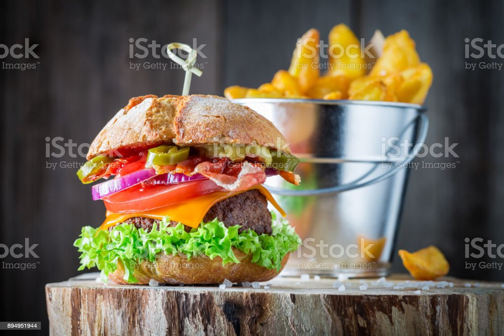 Yummy chips with hamburger made of bacon, tomato and beef stock photo