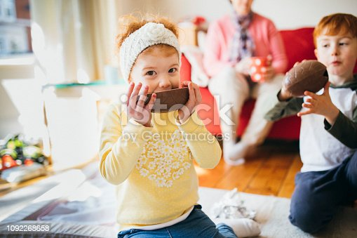 Young siblings eating chocolate easter eggs in their family home.