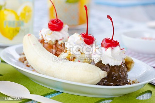 Homemade banana split served for a delicious treat with scoops of vanilla, strawberry and chocolate, drizzled with caramel sauce, nuts, sprinkles,topped with whipped cream and garnished with Maraschino cherries.