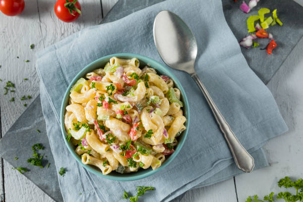 Yummy Homemade Macaroni Salad Yummy Homemade Macaroni Salad with Tomato Onion Celery and Parsley macaroni stock pictures, royalty-free photos & images