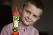Tasty treat or snack made out of fruit. It is in the shape of a rocket to encourage this young boy to eat it! Watermelon, strawberries, banana and kiwi fruit on a wooden kebab stick. The boy is 8 years old. Soft focus on the fruit kebab, making that stand out, with the boy out of focus.