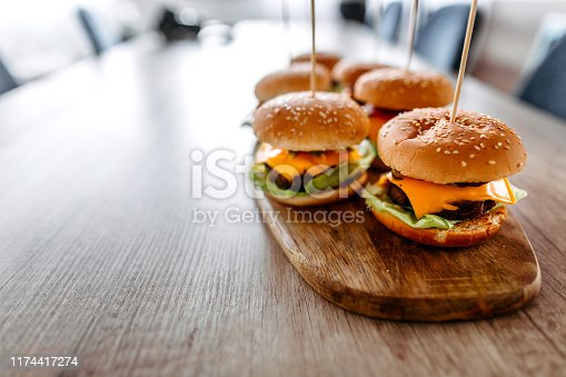 Close up of homemade cheeseburgers on wooden tray served on dining table