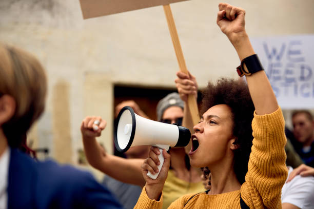yung black woman shouting through megaphone on anti-racism demonstrations. - marciare foto e immagini stock