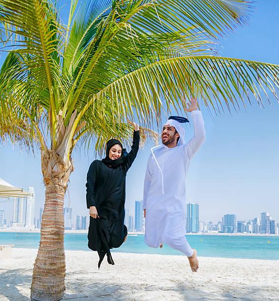 yuppie!  - happy arabische paar springen in der luft - hochzeitsreise dubai stock-fotos und bilder