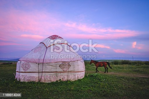 Many horses pass the yurt in grassland in Xinjiang, China