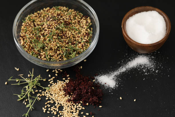 Za'Atar And Ingredients A high angle close up horizontal photograph of a bowl and some of the ingredients for Za'atar a popular spice or condiment used in Middle Eastern cooking. Isolated on black. zaatar spice stock pictures, royalty-free photos & images