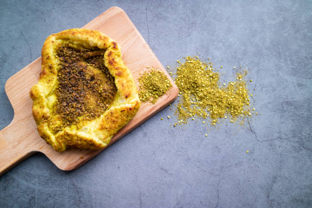 Zaatar Jerusalem bread on a table with some spices on concrete background. Israeli cuisine. Top view. Red Jerusalem pita bread with sesame and Zaatar Jerusalem pita bread on concrete background. Israeli cuisine. zaatar spice stock pictures, royalty-free photos & images