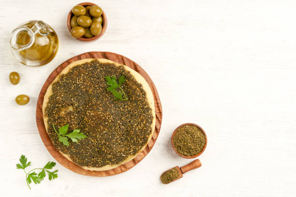Zaatar manakeesh on wooden board with olives and olive oil  . Top view with copy space Food, Arabic cuisine, Zaatar, Breakfast zaatar spice stock pictures, royalty-free photos & images