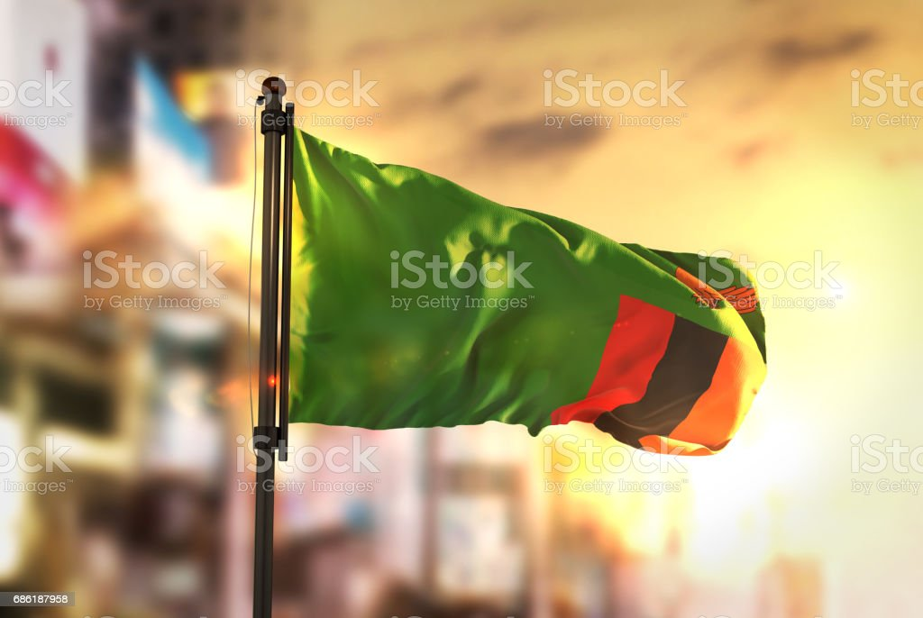Zambia Flag Against City Blurred Background At Sunrise Backlight stock photo