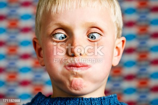 This cute blond 7 year old boy is really having fun, crossing his eyes and blowing out his cheeks as he looks down at his possibly very full mouth! Shot with Canon EOS 1Ds Mark III.