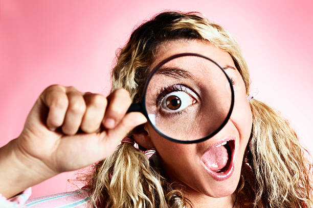 zany blonde looks through magnifying glass with hugely enlarged eye - sherlock holmes stock photos and pictures