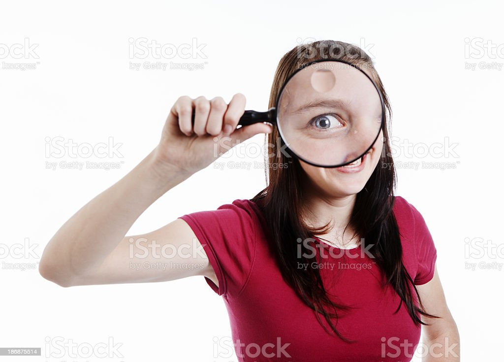 Zany brunette looks through magnifying glass at camera royalty-free stock photo