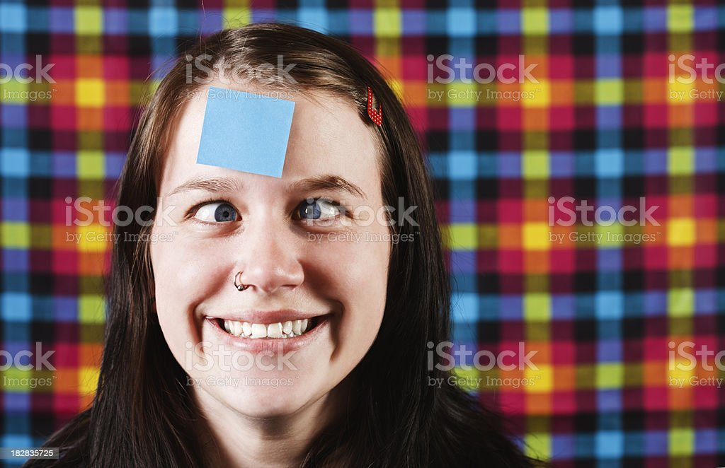 Zany looking girl squints at blue adhesive note on forehead royalty-free stock photo