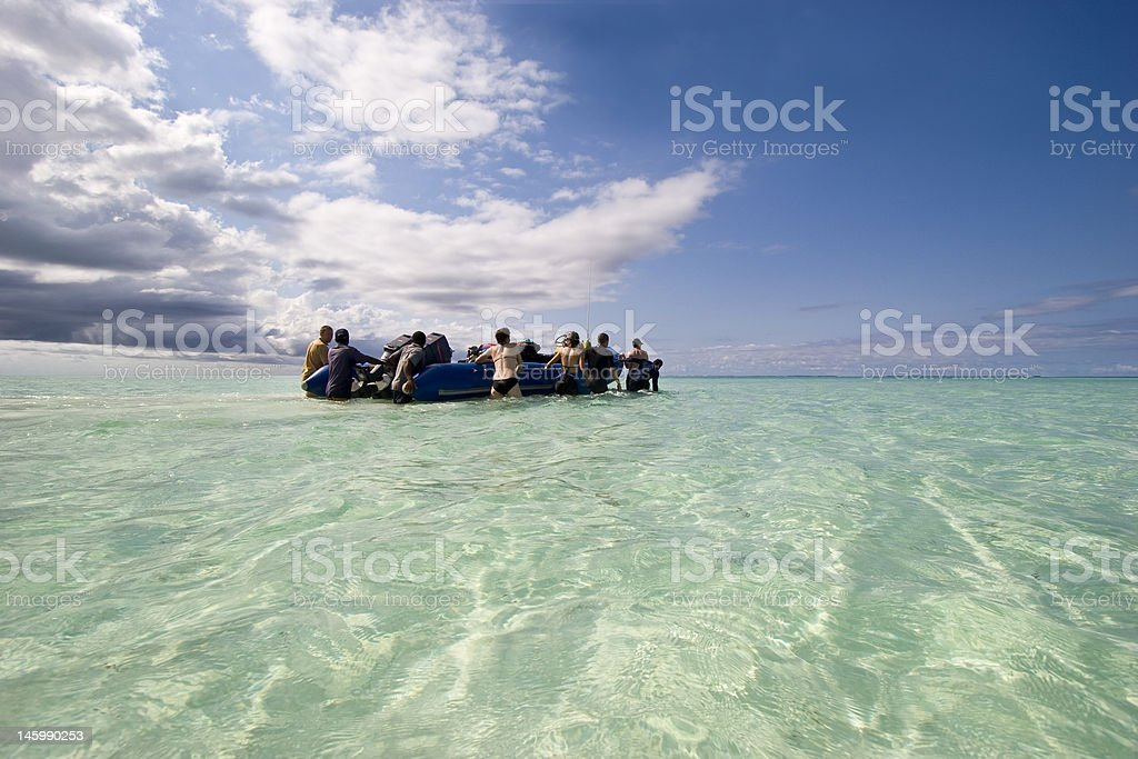 zanzibar diving tourists walking inflatable boat out of shallow 2 royalty-free stock photo
